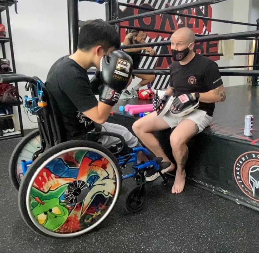 Photo shows Keith in wheelchair having a post-session debrief with his boxing coach after his training.