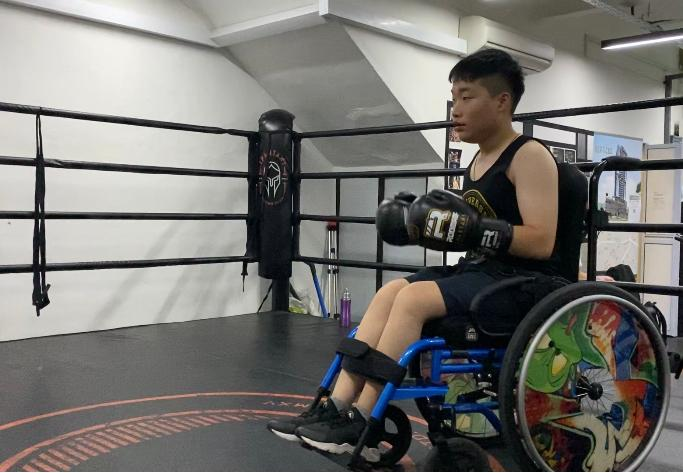 Photo shows Keith Tan wearing his boxing gloves in his wheelchair