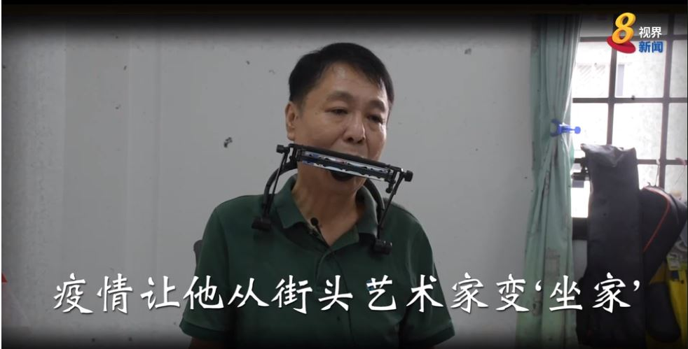 Photo shows Mr William Ngo playing a harmonica.