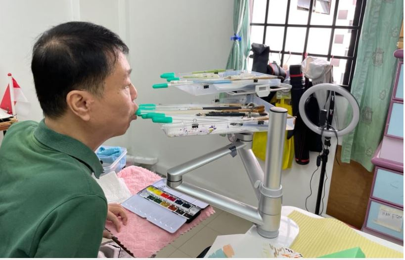 Photo shows Mr William Ngo using his mouth to hold a paint brush.